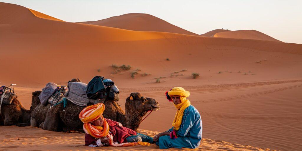 man in yellow robe sitting on brown sand during daytime
